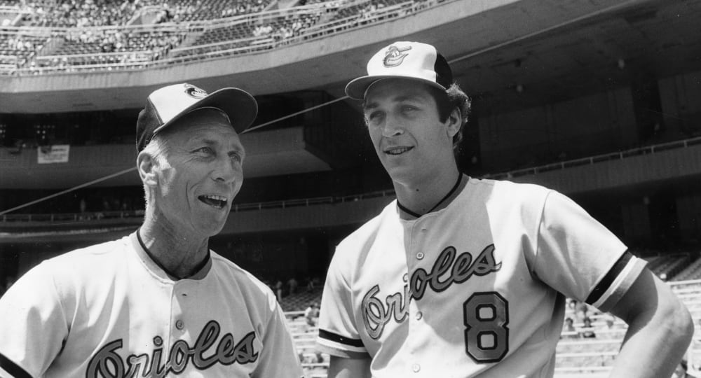 ** FILE ** Baltimore Orioles pitching coach Cal Ripken Sr., left, gets a father's day greeting from his son, Cal Jr., at Yankee Stadium in New York, in this, June 20, 1982 file photo. (AP Photo/Harry Harris)