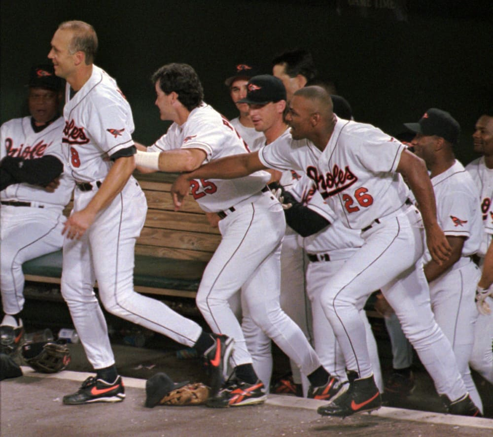 Baltimore Orioles Cal Ripken is pushed out of the dugout by his teammates as they encourage him to take a victory lap after he broke Lou Gehrig's record of 2,130 consecutive games, Wednesday, Sept. 6, 1995 at Baltimore's Camden Yards. (AP Photo/Ted Mathias)
