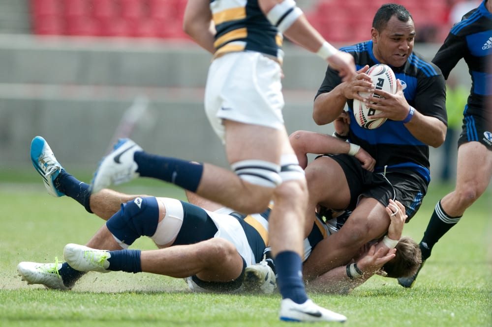 BYU's Paul Lasike is tackled by California players during the Varsity Cup NCAA college rugby championship in Sandy, Utah, Saturday, May 3, 2014. (AP Photo/Daily Herald, Grant Hindsley)