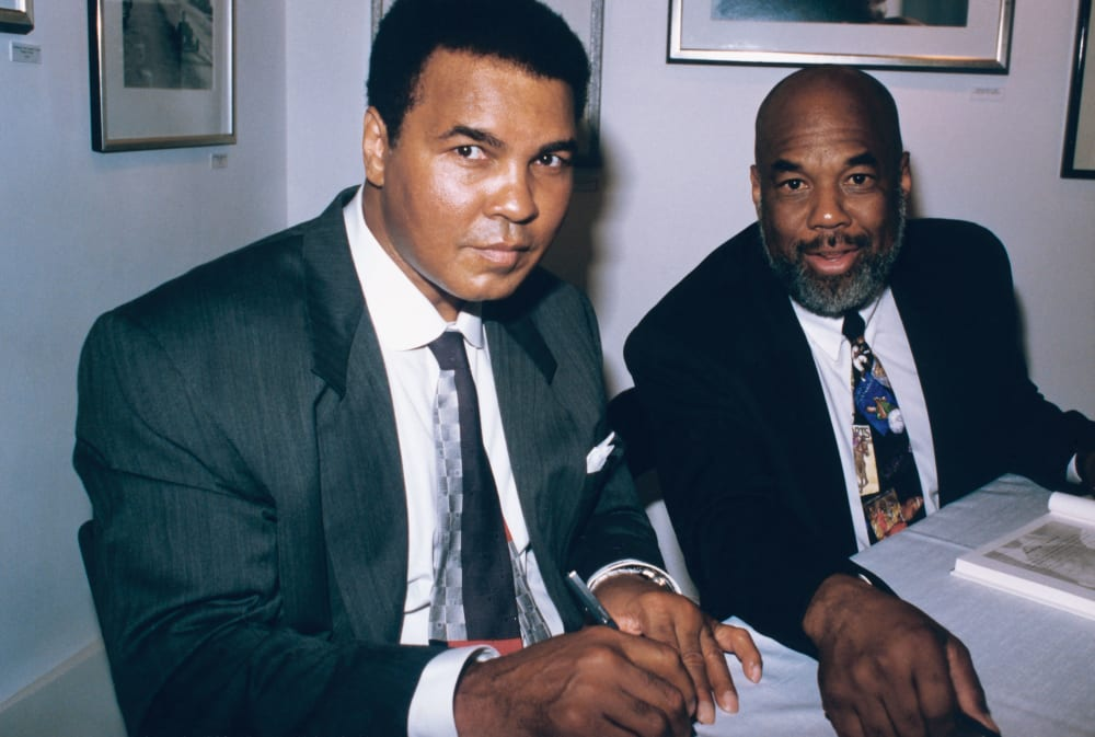 Muhammad Ali and personal photographer Howard Bingham are photographed during Ali's book signing event in 1995. (Frederick Watkins, Jr./Ebony Collection)