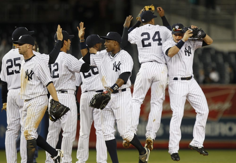 New York Yankees' Nick Swisher, right, and Robinson Cano, second from right, and Curtis Granderson, third from right celebrate with teammates after a baseball game against the Detroit Tigers Saturday, April 2, 2011, at Yankee Stadium in New York. The Yankees won the game 10-6. (AP Photo/Frank Franklin II)
