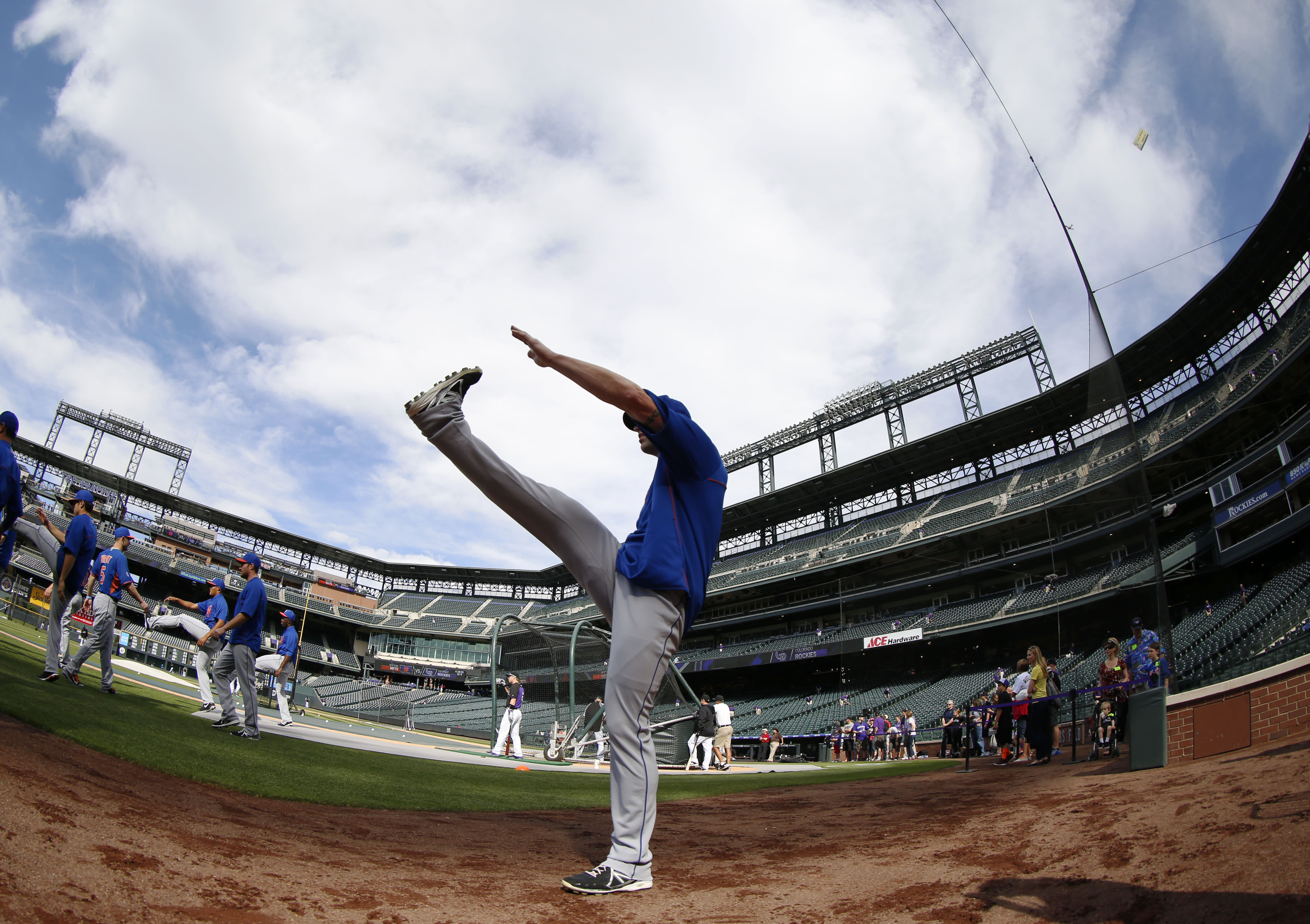 With the help of a fisheye lens, New York Mets pitcher Kyle Farnsworth stretches before facing the Colorado Rockies in the first inning of a baseball game in Denver on Saturday, May 3, 2014. (AP Photo/David Zalubowski)
