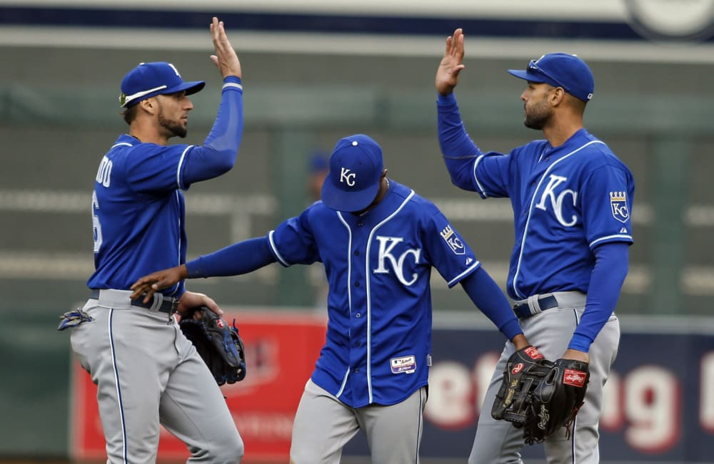 From left to right, Kansas City Royals left fielder Paulo Orlando, center fielder Jarrod Dyson and right fielder Alex Rios celebrate a 6-1 win over the Minnesota Twins in a baseball game Sunday, Oct. 4, 2015, in Minneapolis. (AP Photo/Bruce Kluckhohn)