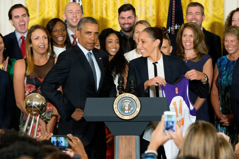 President Barack Obama puffs out his chest as former Phoenix Mercury guard Diana Taurasi presents him with an XL jersey in the East Room of the White House in Washington, Wednesday, Aug. 26, 2015, during a ceremony where the president honored the 2014 WNBA basketball Champions Phoenix Mercury. (AP Photo/Andrew Harnik)