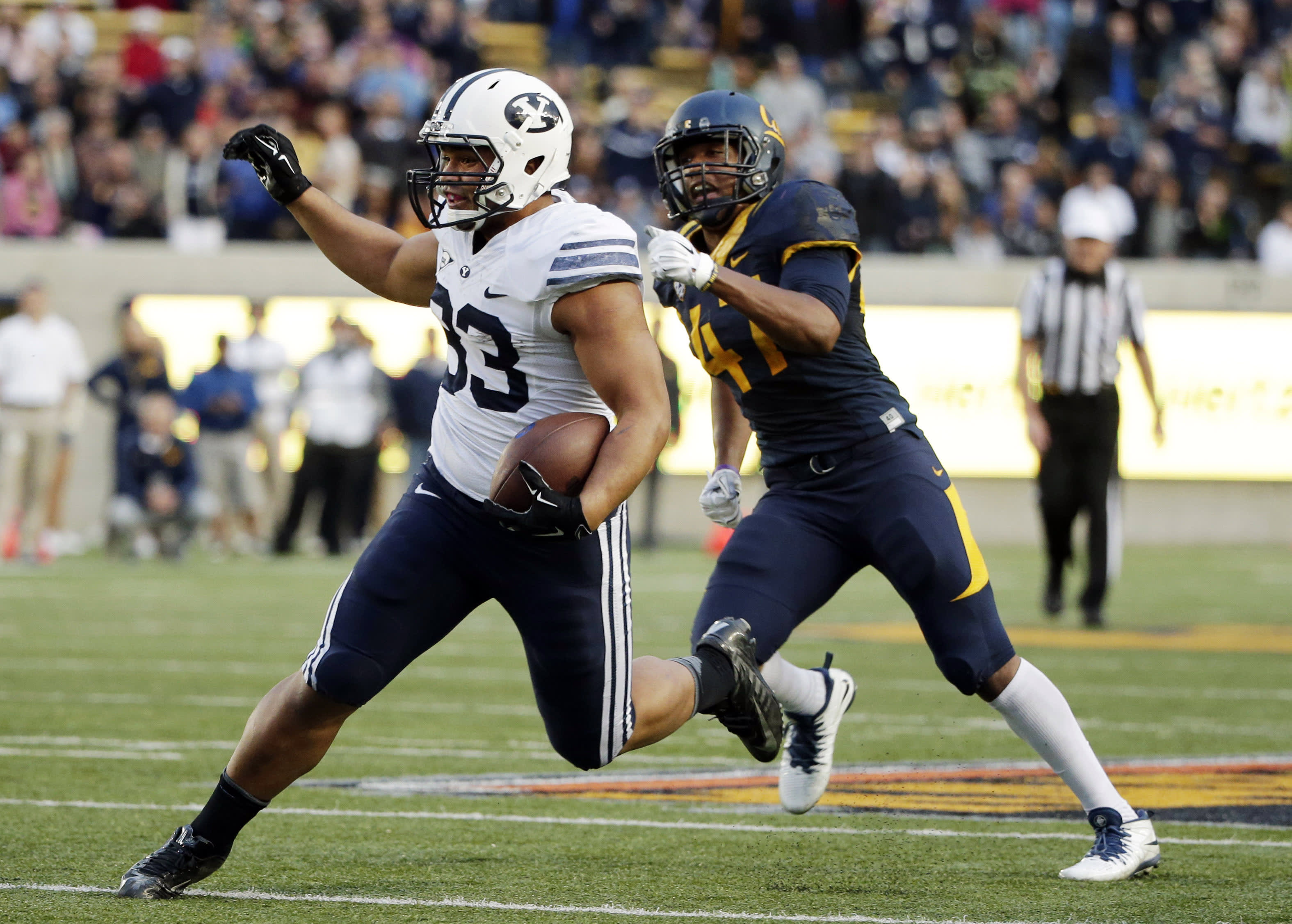 BYU running back Paul Lasike (33) runs past California linebacker Hardy Nickerson during the second half of an NCAA college football game, Saturday, Nov. 29, 2014, in Berkeley, Calif. BYU won 42-35. (AP Photo/Marcio Jose Sanchez)