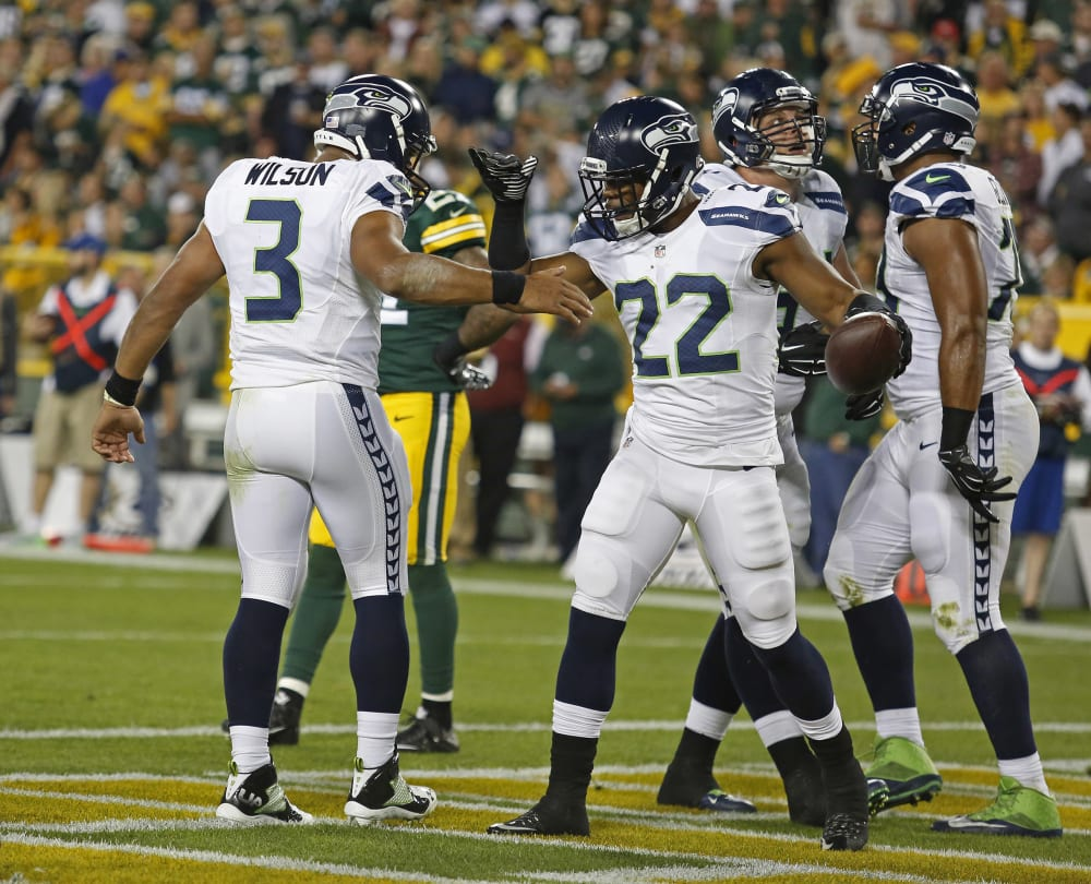 Seattle Seahawks quarterback Russell Wilson (3) and running back Fred Jackson (22) celebrate a touchdown against the Green Bay Packers during an NFL football game Sunday Sept. 20, 2015, in Green Bay, Wis. (AP Photo/Matt Ludtke)