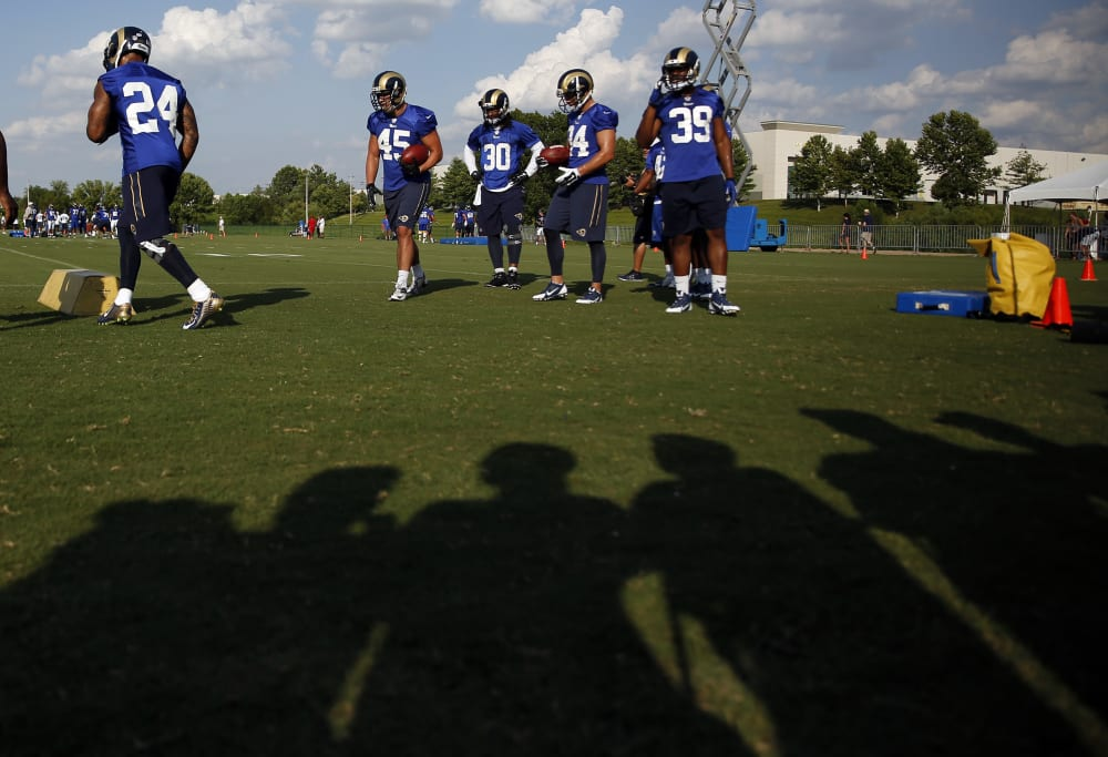 Members of the St. Louis Rams practice as the silhouettes of fans are seen on the turf as they watch during training camp at the NFL football team's practice facility Sunday, Aug. 2, 2015, in St. Louis. (AP Photo/Jeff Roberson)