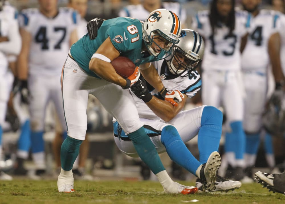 Miami Dolphins' Chris Hogan (81) is tackled by Carolina Panthers' Kion Wilson (42) during the fourth quarter of a preseason NFL football game in Charlotte, N.C., Friday, Aug. 17, 2012. The Panthers won 23-17. (AP Photo/Bob Leverone)