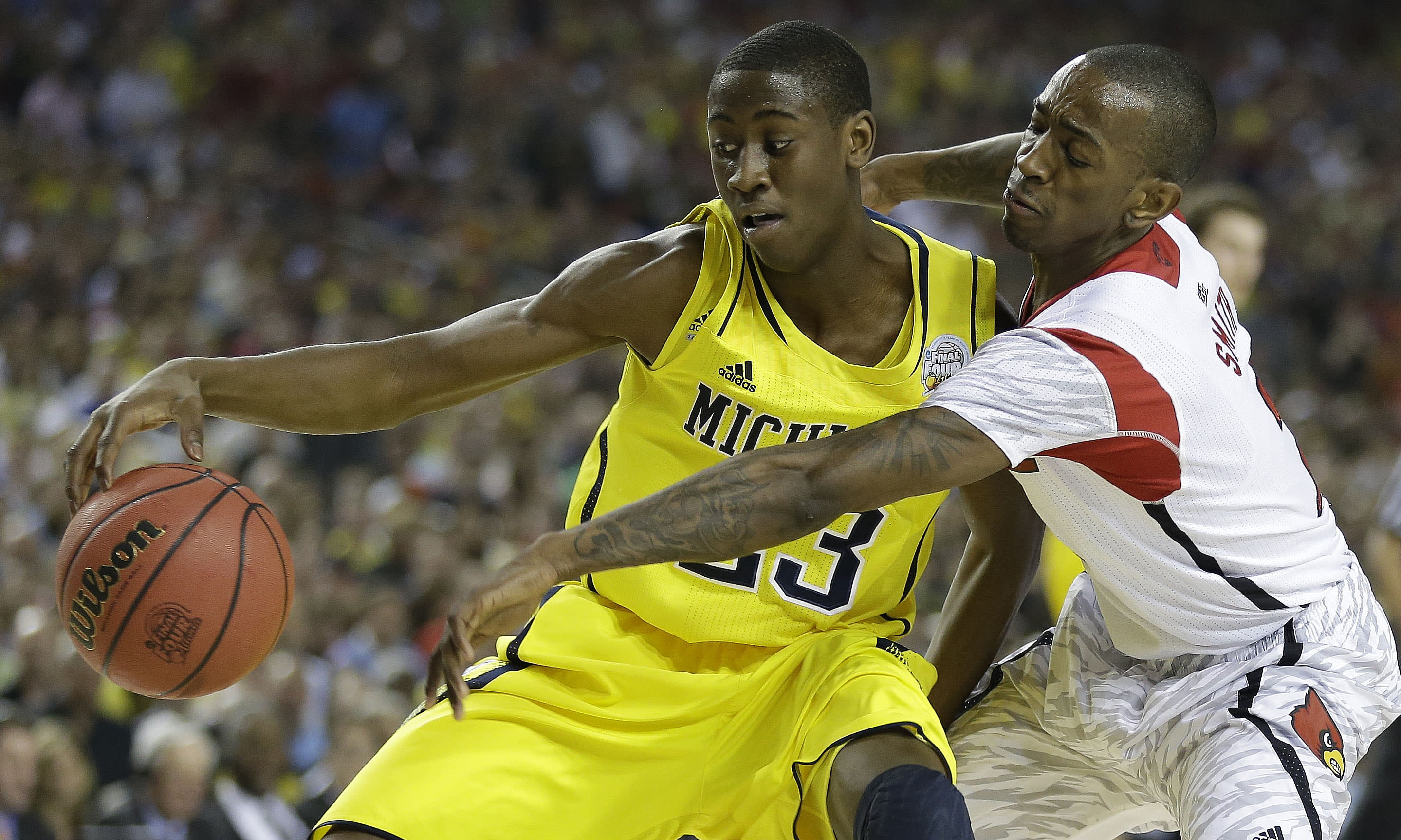 Louisville guard Russ Smith (2) and Michigan guard Caris LeVert (23) vie for a loose ball during the first half of the NCAA Final Four tournament college basketball championship game Monday, April 8, 2013, in Atlanta. (AP Photo/Charlie Neibergall)
