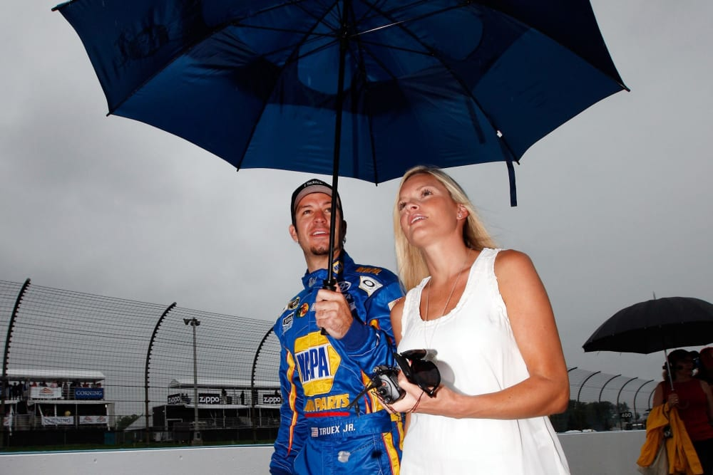 WATKINS GLEN, NY - AUGUST 14: Martin Truex Jr., driver of the #56 NAPA Auto Parts Toyota, walks off the grid with his girlfriend Sherry Pollex as it starts to rain before the NASCAR Sprint Cup Series Heluva Good! Sour Cream Dips at the Glen at Watkins Glen International on August 14, 2011 in Watkins Glen, New York. (Photo by Chris Graythen/Getty Images)
