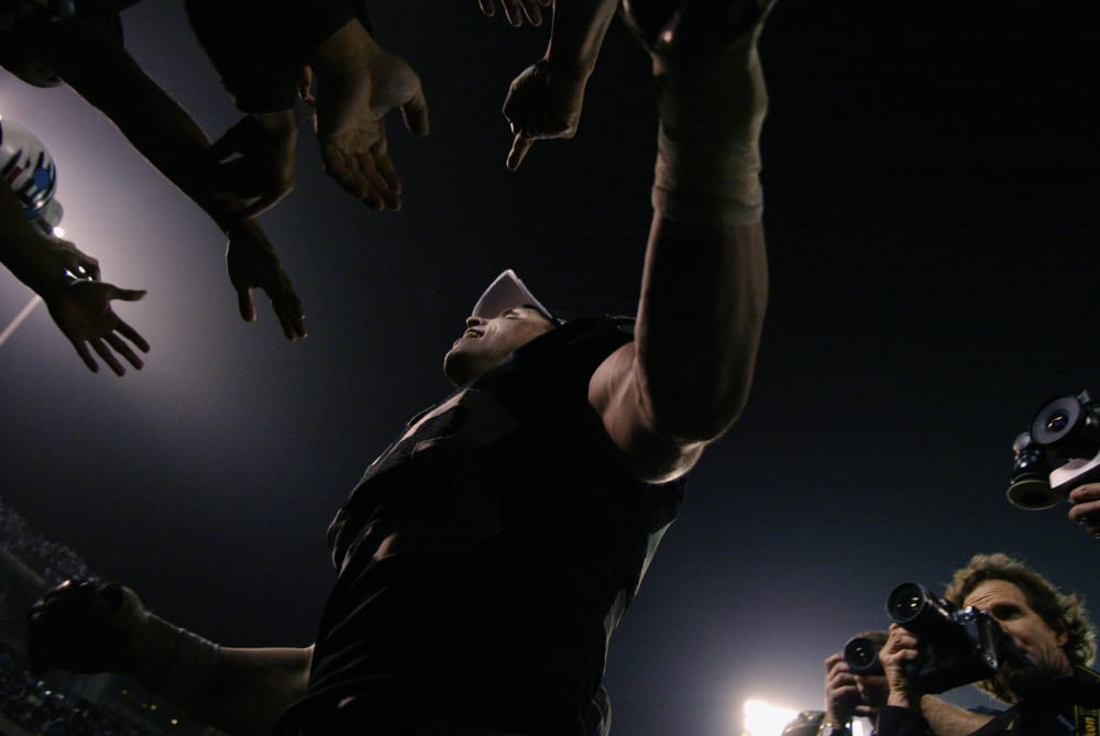 OAKLAND, CA - JANUARY 19:  Linebacker Bill Romanowski #53 of the Oakland Raiders slaps hands with the fans in the Black Hole after defeating the Tennessee Titans in the AFC Championship game at Network Associates Coliseum January 19, 2003 in Oakland, California.  The Raiders defeated the Titans 41-24, sending them on to the NFL title game for the first time since 1984.  (Photo by Brian Bahr/Getty Images)