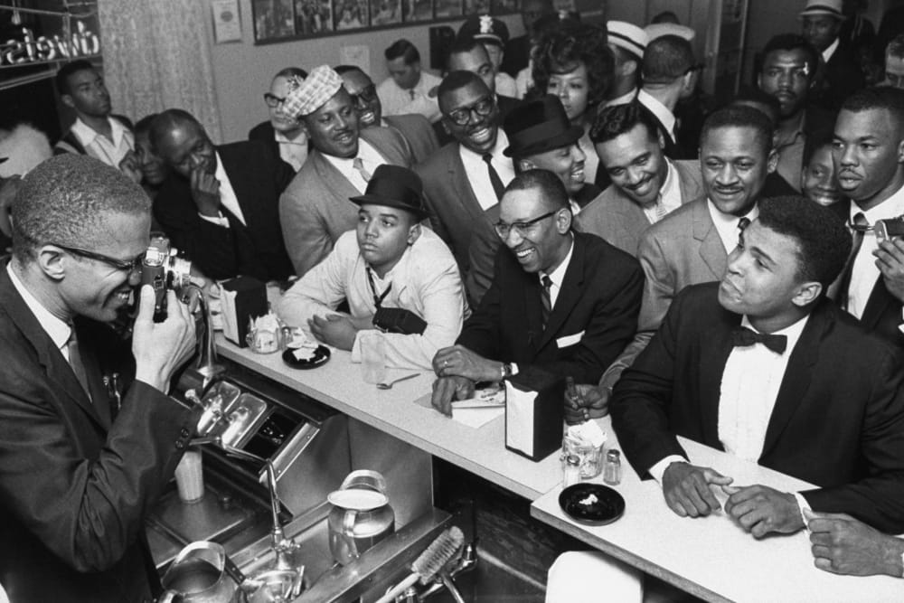 MARCH 1964 - MIAMI: Black Muslim leader Malcolm X (L) behind soda fountain training his camera on tux-clad Cassius Clay (now Muhammad Ali) (R) sitting at counter surrounded by jubilant fans after he beat Sonny Liston for the heavyweight championship of the world. (Photo by Bob Gomel/The LIFE Images Collection/Getty Images)