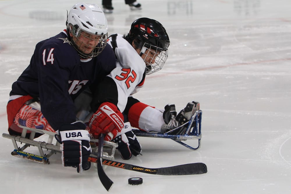 VANCOUVER, BC - MARCH 20:  Josh Pauls #14 of the United States battles for the puck against Daisuke Uehara #32 of Japan during the second period of the Ice Sledge Hockey Gold Medal Game on day nine of the 2010 Vancouver Winter Paralympic Games at UBC Thunderbird Arena on March 20, 2010 in Vancouver, Canada.  (Photo by Martin Rose/Bongarts/Getty Images)