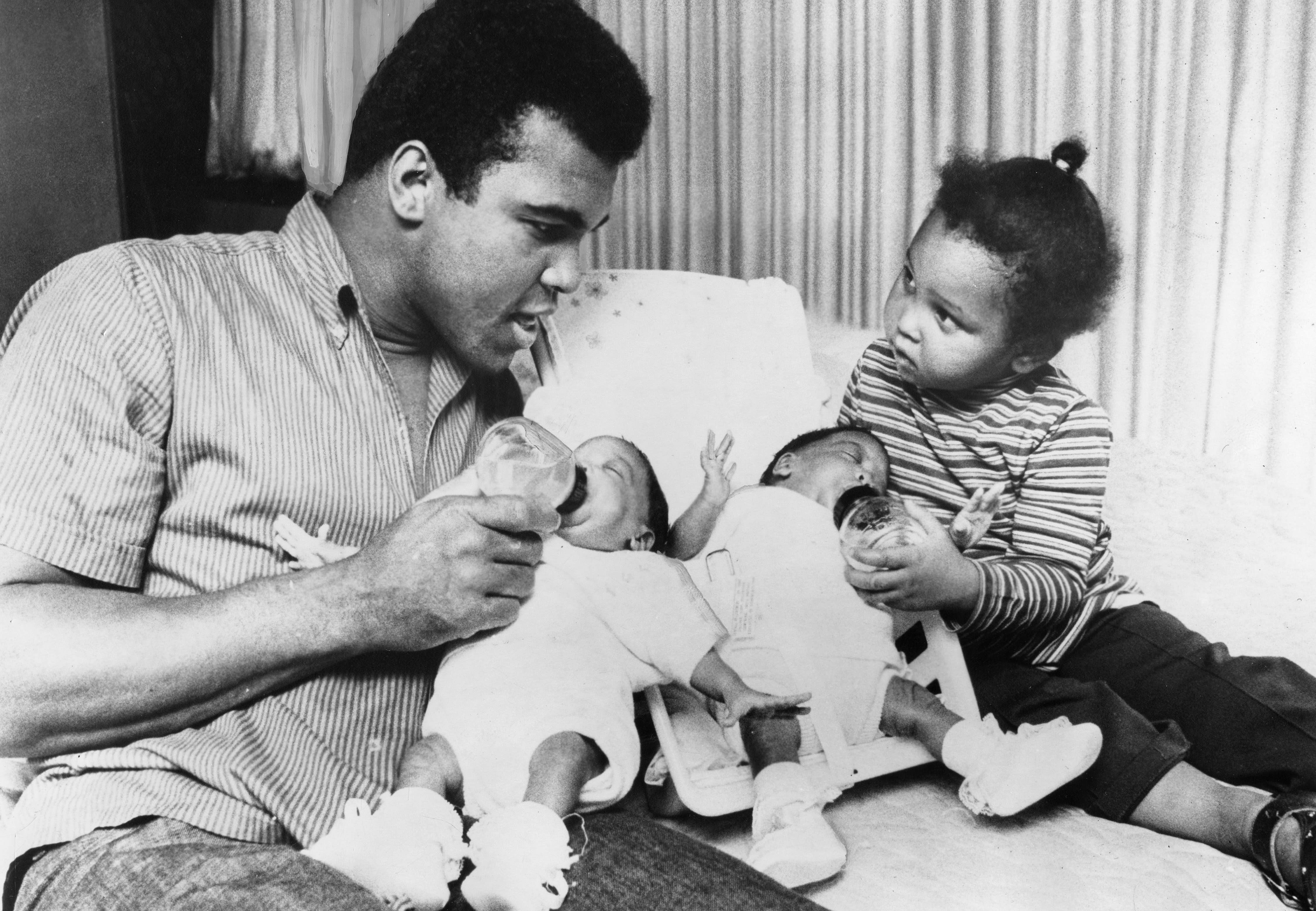 Unknown date and location; USA: FILE PHOTO; Cassius Clay aka Muhammad Ali and his daughter Maryum Ali feed his 3 month old twins Reshemah Ali and Jamillah Ali in 1970. Mandatory Credit: The Courier-Journal-USA TODAY Sports